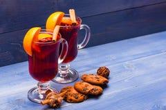 Exponeringsglas med den funderade vin eller drinken nära chokladkakor på träbakgrund Drink eller dryck med kanelbruna pinnar royaltyfri foto