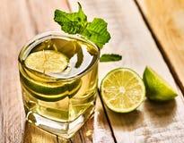 Exponeringsglas med den gröna genomskinliga den limefruktdrinken och mintkaramellen Arkivfoto