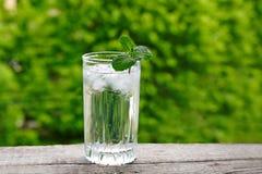 Exponeringsglas med den isvatten och mintkaramellen på en trätabell Royaltyfri Fotografi