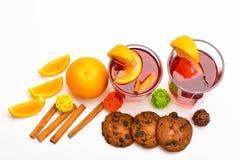 Exponeringsglas med den varma drinken nära saftig orange frukt på vit bakgrund, slut upp Drink eller dryck med kanelbruna pinnar Royaltyfri Fotografi