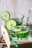 Exponeringsglas med detoxgurkavatten med limefrukt och mintkaramellen på ett trämagasin, kanna, sommar eller vår Fotografering för Bildbyråer