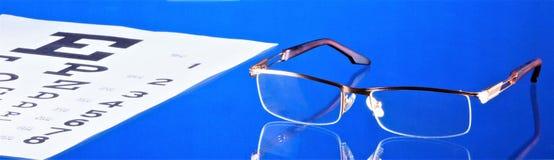 Exponeringsglas med diopters och provtabellen för visuell skärpa Exponeringsglas - optisk apparat för visionkorrigering Tabell me arkivbilder