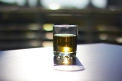 Exponeringsglas med drycken på den svarta överkanten royaltyfri foto