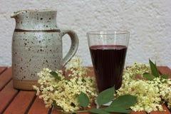 Exponeringsglas med fläderbärfruktsaft som omges av elderflowers Arkivbilder