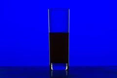 Exponeringsglas med fruktsaft med blå bakgrund Royaltyfria Foton