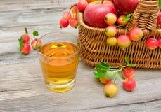 Exponeringsglas med fruktsaft och äpplen i en korg Arkivbilder