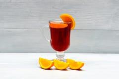 Exponeringsglas med funderat vin nära saftig orange frukt Varmt rött funderat vin som isoleras på vit bakgrund med julkryddor Royaltyfri Fotografi