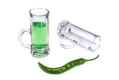 Exponeringsglas med grön absint- och chilipeppar på vit bakgrund Fotografering för Bildbyråer