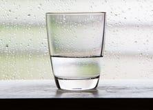 Exponeringsglas med halva per exponeringsglas av vattenplatser med kondensationsexponeringsglas Royaltyfria Foton