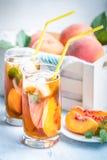 Exponeringsglas med hemlagat iste, smaksatt persika Klipp nytt persikaskivor för ordning Vit spjällåda mycket med persikor i baks Arkivbild