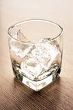 Exponeringsglas med iskuber på trätabellen Arkivbilder