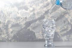 Exponeringsglas med isvatten och en flaska av vatten på en grå bakgrund Fotografering för Bildbyråer