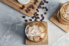 Exponeringsglas med kallt brygdkaffe och mjölkar arkivfoto