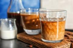 Exponeringsglas med kallt brygdkaffe och mjölkar royaltyfri foto