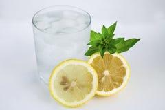 Exponeringsglas med kallt vatten, citronen och mintkaramellen Kallt vatten p? en vit bakgrund royaltyfria foton