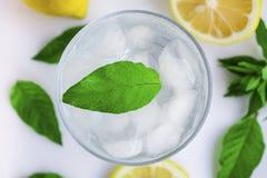 Exponeringsglas med kallt vatten, citronen och mintkaramellen Kallt vatten p? en vit bakgrund arkivfoton