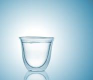 Exponeringsglas med kolsyrat vatten på blå lutningbakgrund Fotografering för Bildbyråer