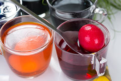 Exponeringsglas med kulöra matfärger för traditionell färgläggning för påskägg och påskägg och påskliljor Arkivbilder