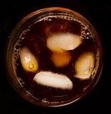 Exponeringsglas med mörkt vätske mycket med iskuber fotografering för bildbyråer
