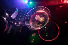 Exponeringsglas med martini med oliv inom på dj-kontrollant i nattklubb Dj-konsol med klubbadrinken på musikpartiet i nattklubb m Royaltyfria Bilder