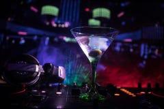 Exponeringsglas med martini med oliv inom på dj-kontrollant i nattklubb Dj-konsol med klubbadrinken på musikpartiet i nattklubb m Arkivfoto