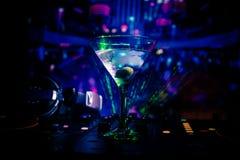 Exponeringsglas med martini med oliv inom på dj-kontrollant i nattklubb Dj-konsol med klubbadrinken på musikpartiet i nattklubb m Arkivbild