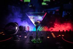 Exponeringsglas med martini med oliv inom på dj-kontrollant i nattklubb Dj-konsol med klubbadrinken på musikpartiet i nattklubb m Royaltyfri Fotografi