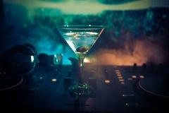 Exponeringsglas med martini med oliv inom på dj-kontrollant i nattklubb Dj-konsol med klubbadrinken på musikpartiet i nattklubb m Arkivbilder