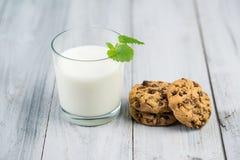 Exponeringsglas med mjölkar, mintkaramellsidor och choklade kakor på en träbakgrund Royaltyfri Fotografi
