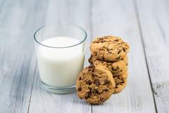 Exponeringsglas med mjölkar och choklade kakor på träbakgrund Fotografering för Bildbyråer