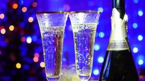 Exponeringsglas med mousserande vin och flaskan på bokehbakgrundsgirlander Fotografering för Bildbyråer