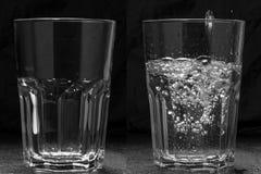Exponeringsglas med och utan vatten på en svart bakgrund Begreppet av optimism och pessimism arkivfoto