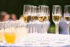 Exponeringsglas med olika alkohol- och nonalcoholdrinkar: champagne och fruktsaft Royaltyfria Foton