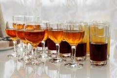 Exponeringsglas med olika drinkar på cocktailpartyet Royaltyfri Foto