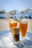 Exponeringsglas med orange fruktsaft och frappe på en tabell i den traditionella grekiska krogen Royaltyfri Bild