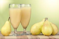Exponeringsglas med päronfruktsaft arkivfoton