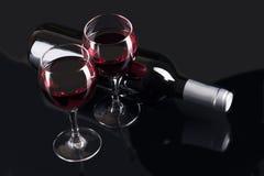 Exponeringsglas med rött vin och den svarta flaskan Royaltyfri Fotografi