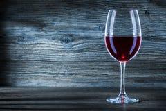 Exponeringsglas med rött vin på wintageträslut upp sikt arkivfoto