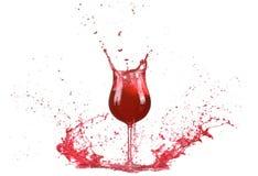 Exponeringsglas med rött vin, rött vinfärgstänk, vin som häller på tabellen som omkring isoleras på vit bakgrund, stor färgstänk Royaltyfria Bilder