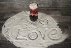 Exponeringsglas med rosa och uttryck av förälskelse i sanden Royaltyfria Foton