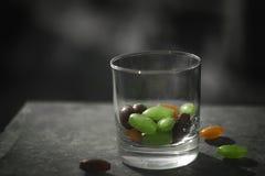 Exponeringsglas med sötsaker på tabellen för barn royaltyfria bilder