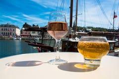 Exponeringsglas med smaklig äppelcider och den rosa vinrankan i gammal fransk fisherm arkivfoto