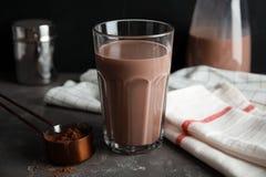 Exponeringsglas med smaklig choklad mjölkar på den gråa tabellen royaltyfri fotografi