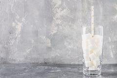 Exponeringsglas med sockerkuber är ett sjukligt bantar Innehållet av socker i söt sodavatten royaltyfri foto