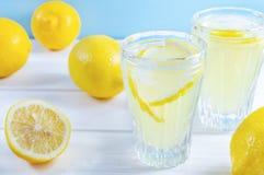 Exponeringsglas med sommardrinklemonad och citronfrukt på den vita trätabellen royaltyfri foto