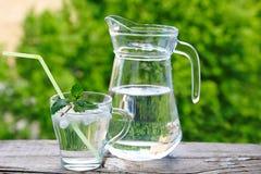 Exponeringsglas med sugrör, isvatten och mintkaramellen Arkivfoton