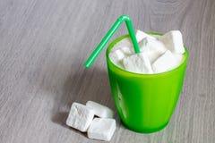 Exponeringsglas med sugrör som är fullt av socker Arkivbild