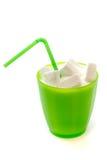 Exponeringsglas med sugrör som är fullt av socker arkivfoton