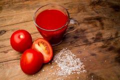 Exponeringsglas med tomatfruktsaft och mogna tomater på en trätabell arkivbild