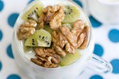 Exponeringsglas med vanlig yoghurt med kiwin och muttrar Royaltyfria Foton